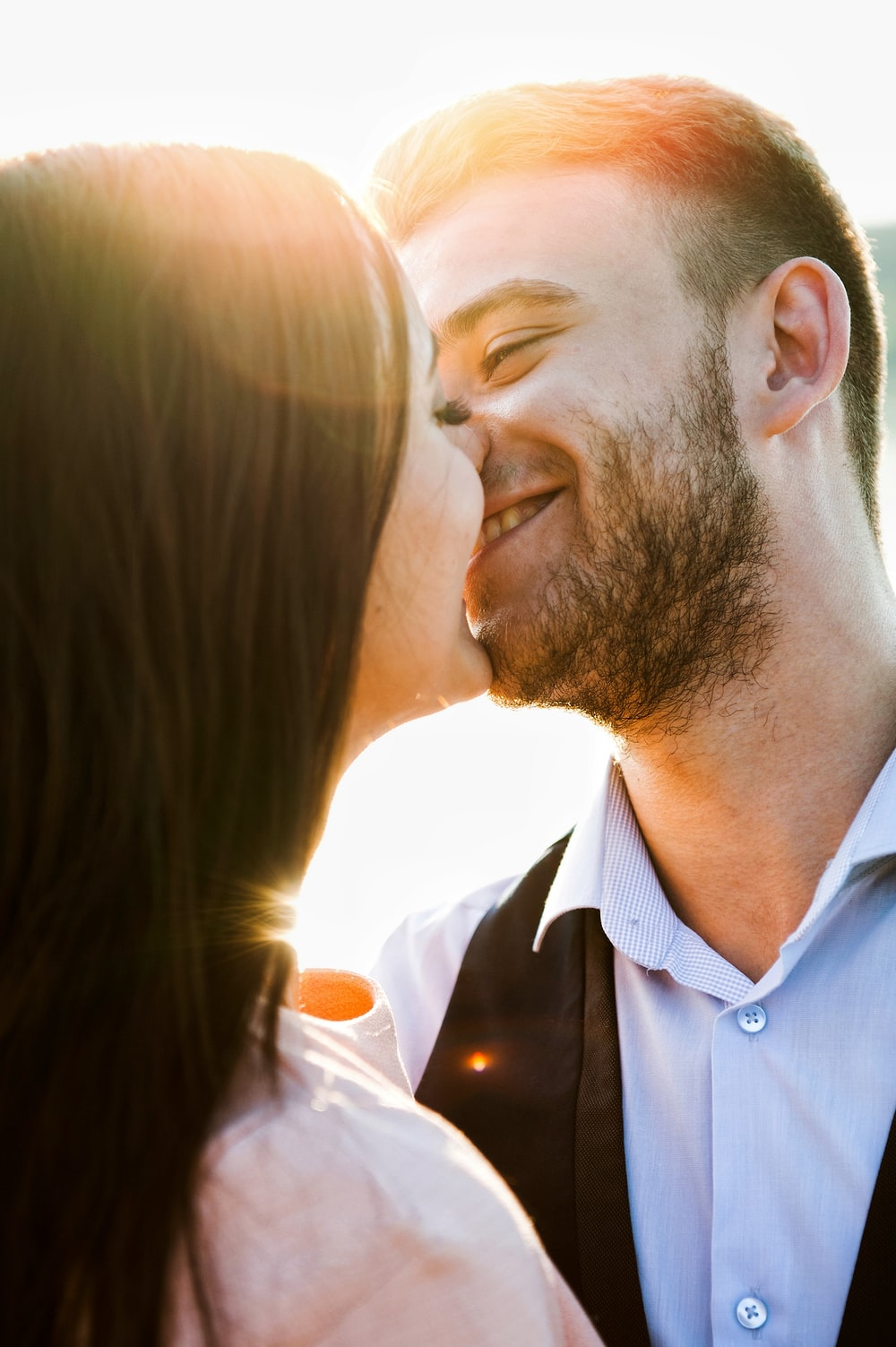 smiling coupe kissing with sun rays during daytime