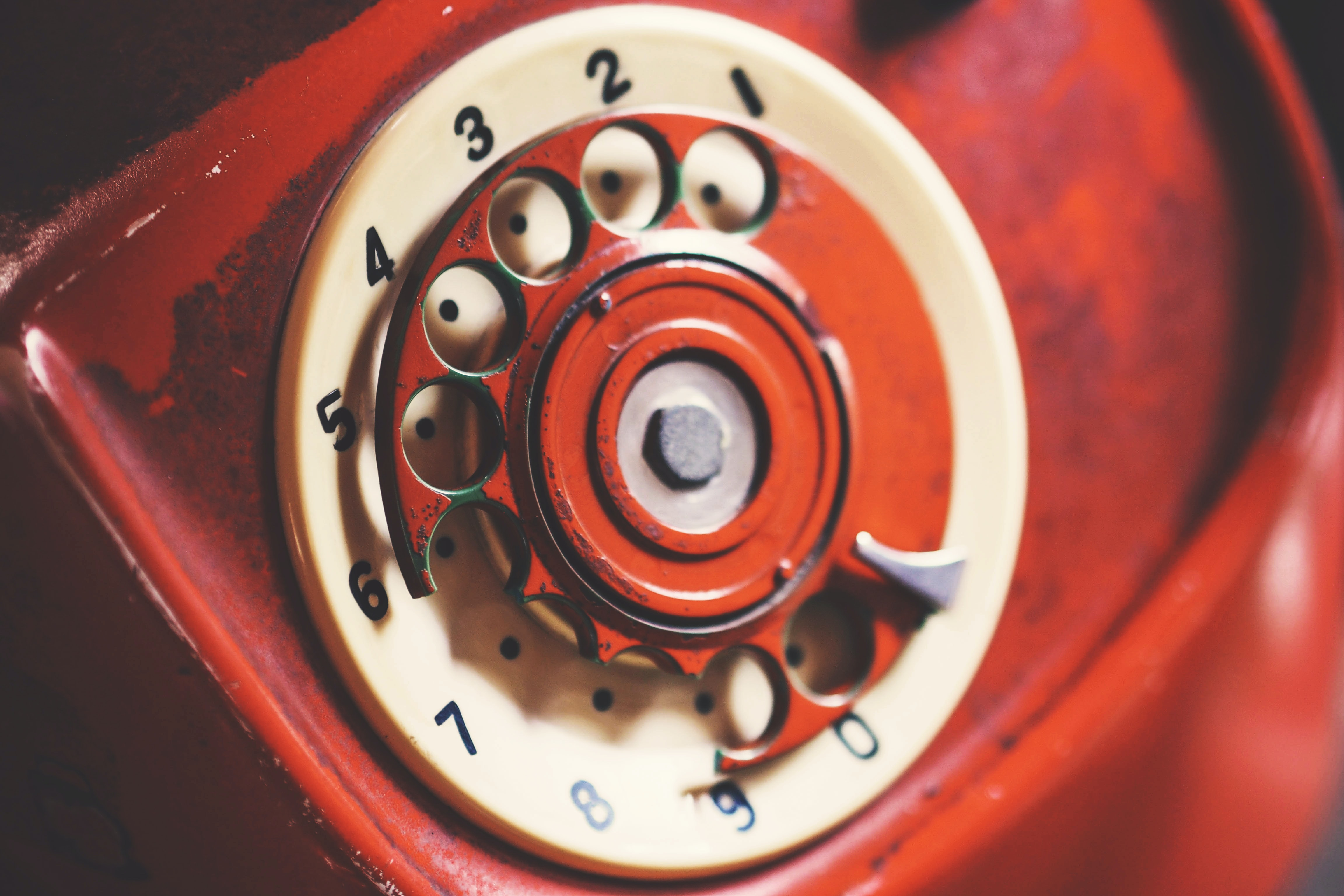 focus photo of red and white rotary telephone