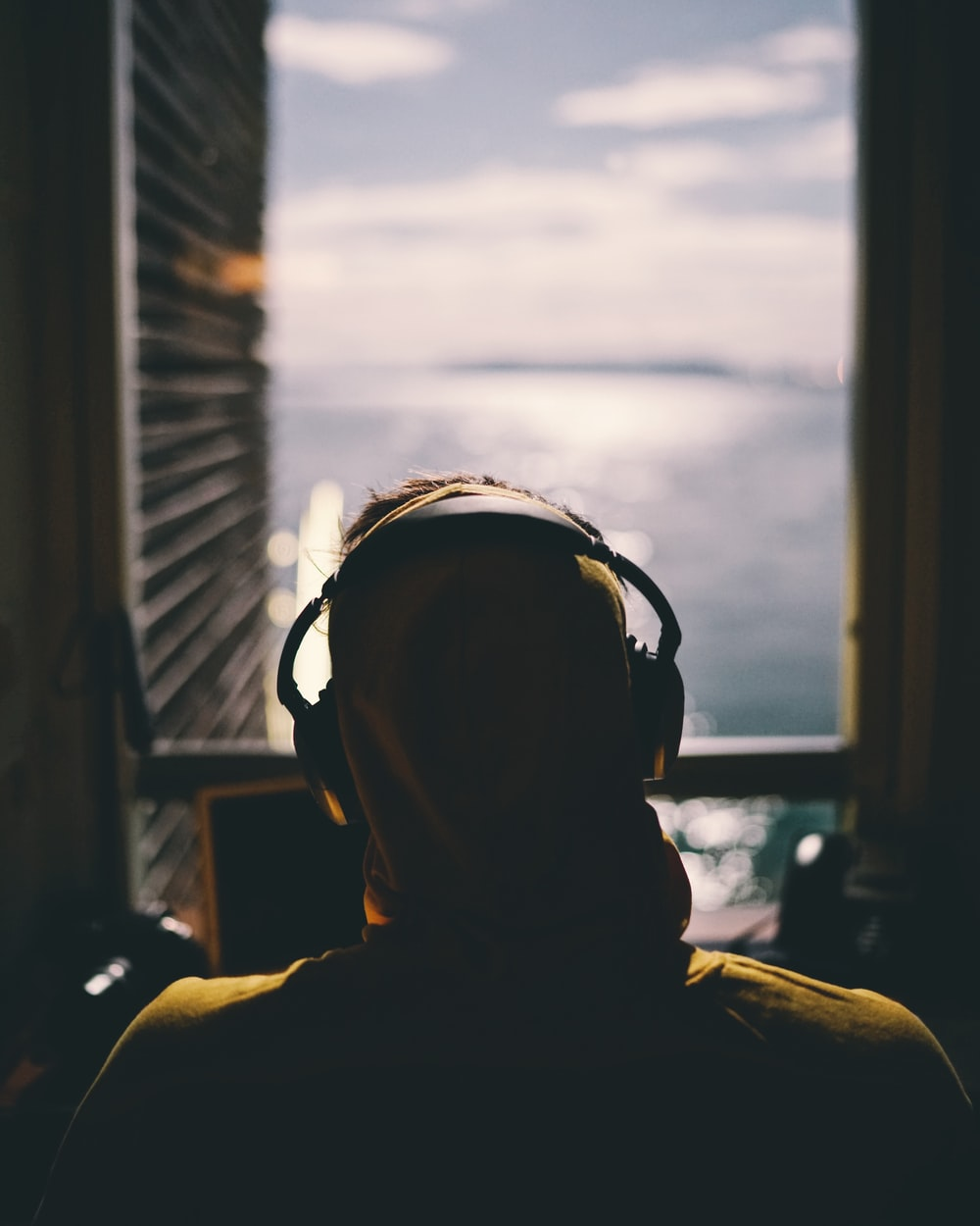 tilt-shift lens photography of person wearing headphones facing body of water through window of a dark room