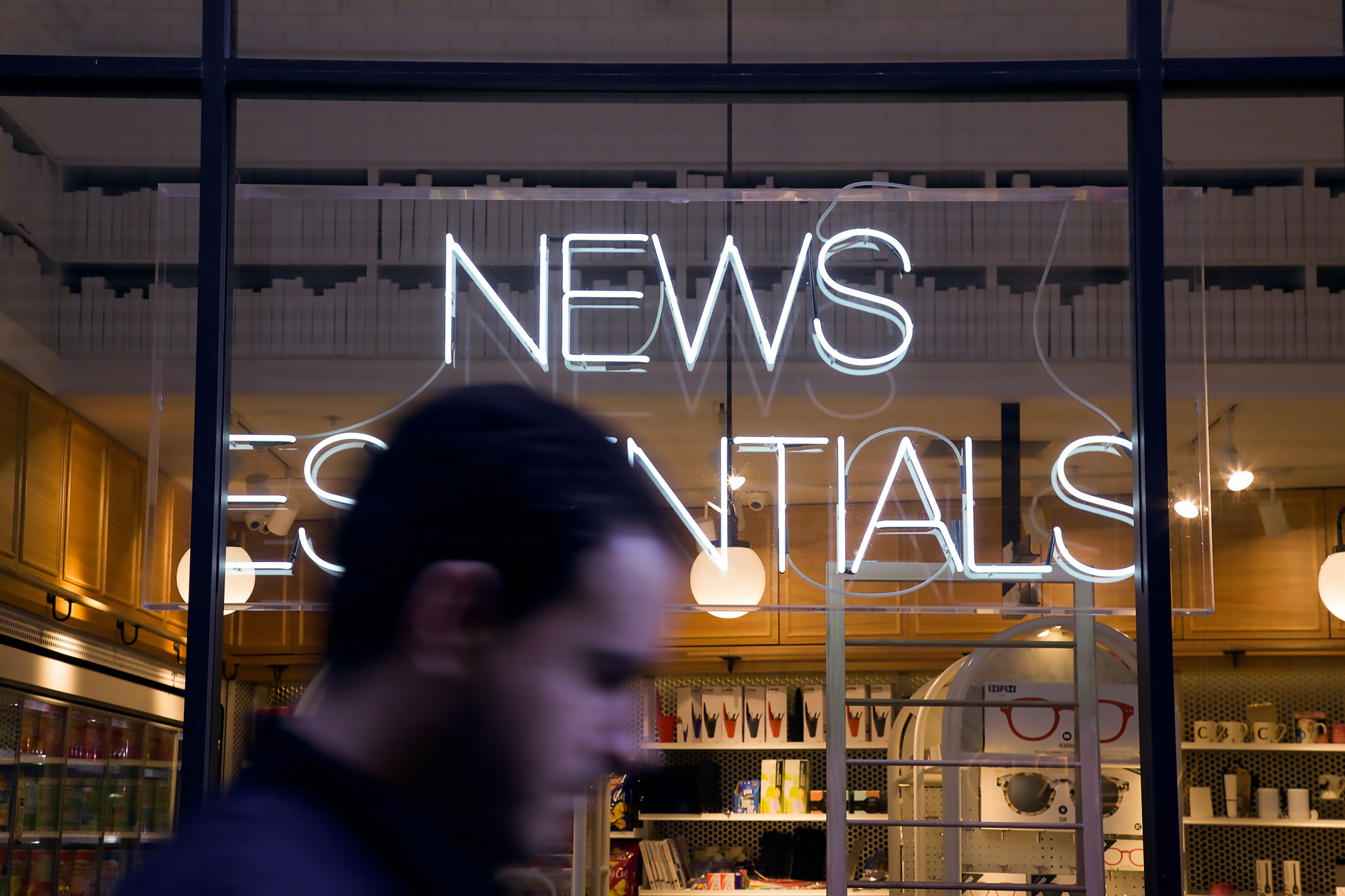 photo of man walking past by News Essentials store