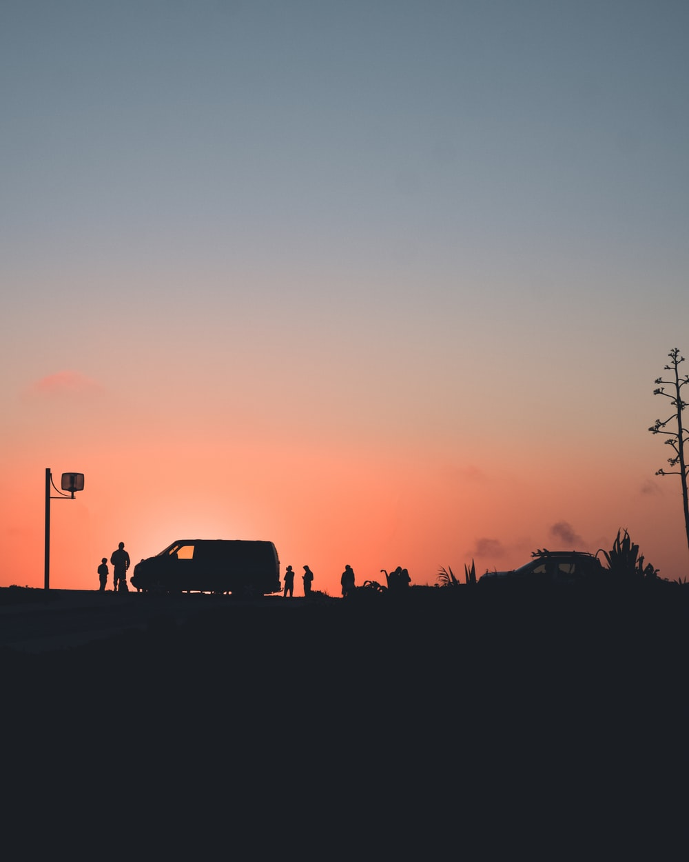 silhouette photo of people gathering outside vehicle