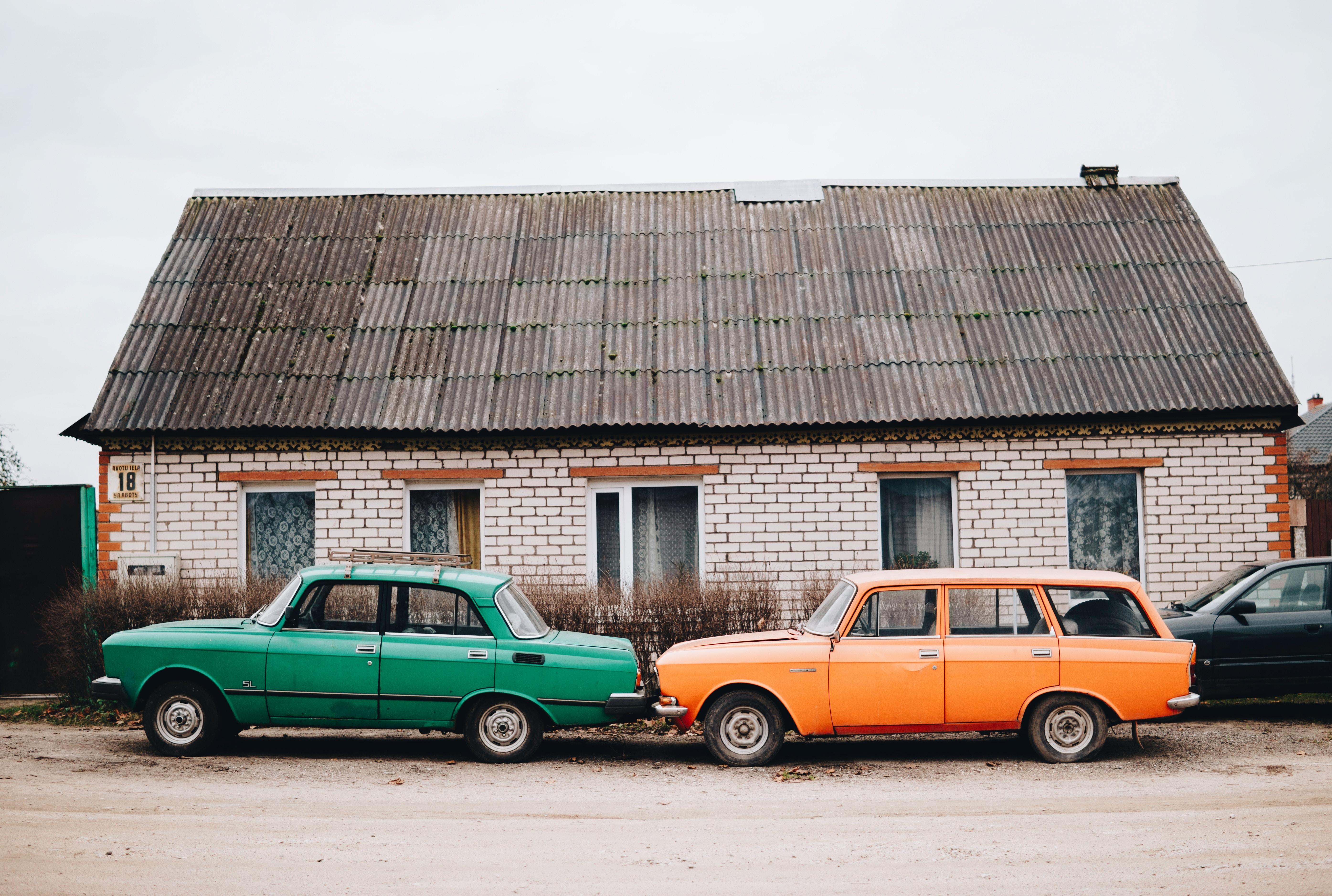 green sedan and orange station wagon beside building