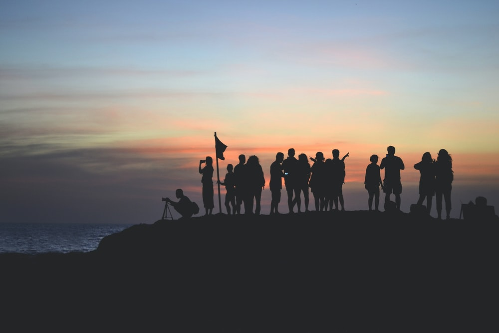 silhouette photography of people gathered together on cliff