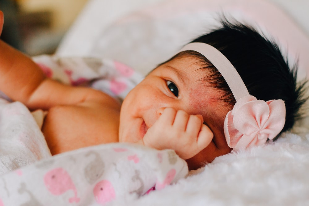 baby wearing white floral headband lying on bed while smiling