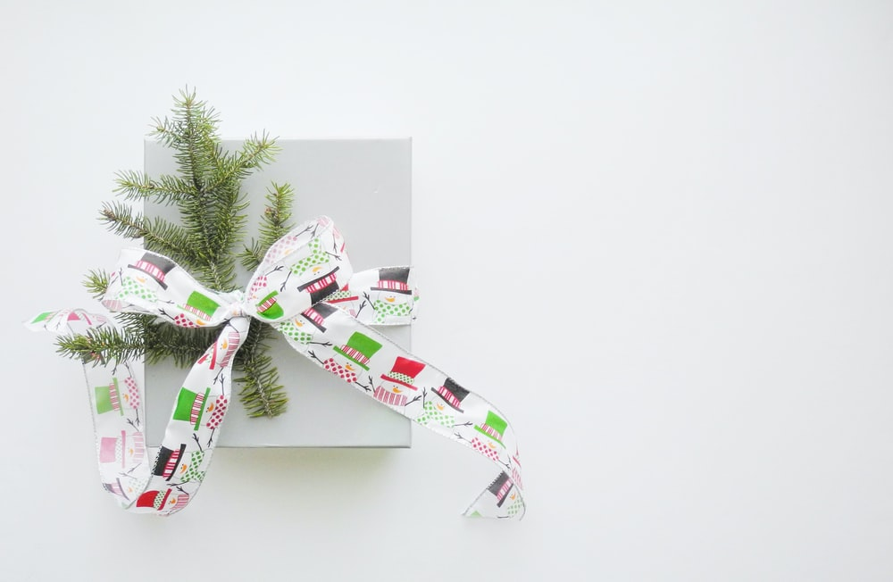green pine tree leaves tied with multicolored fabric strap ribbon