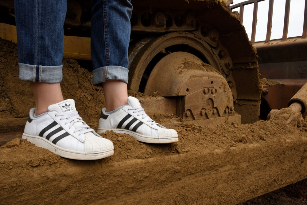 person wearing blue denim jeans and white adidas sneakers