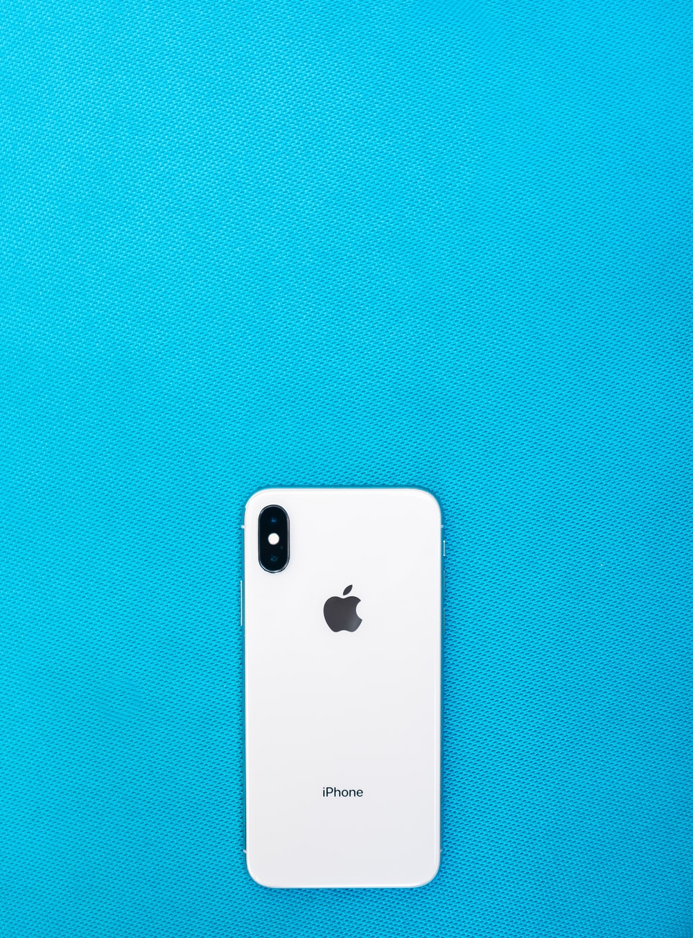 post-2017 iPhone on teal surface