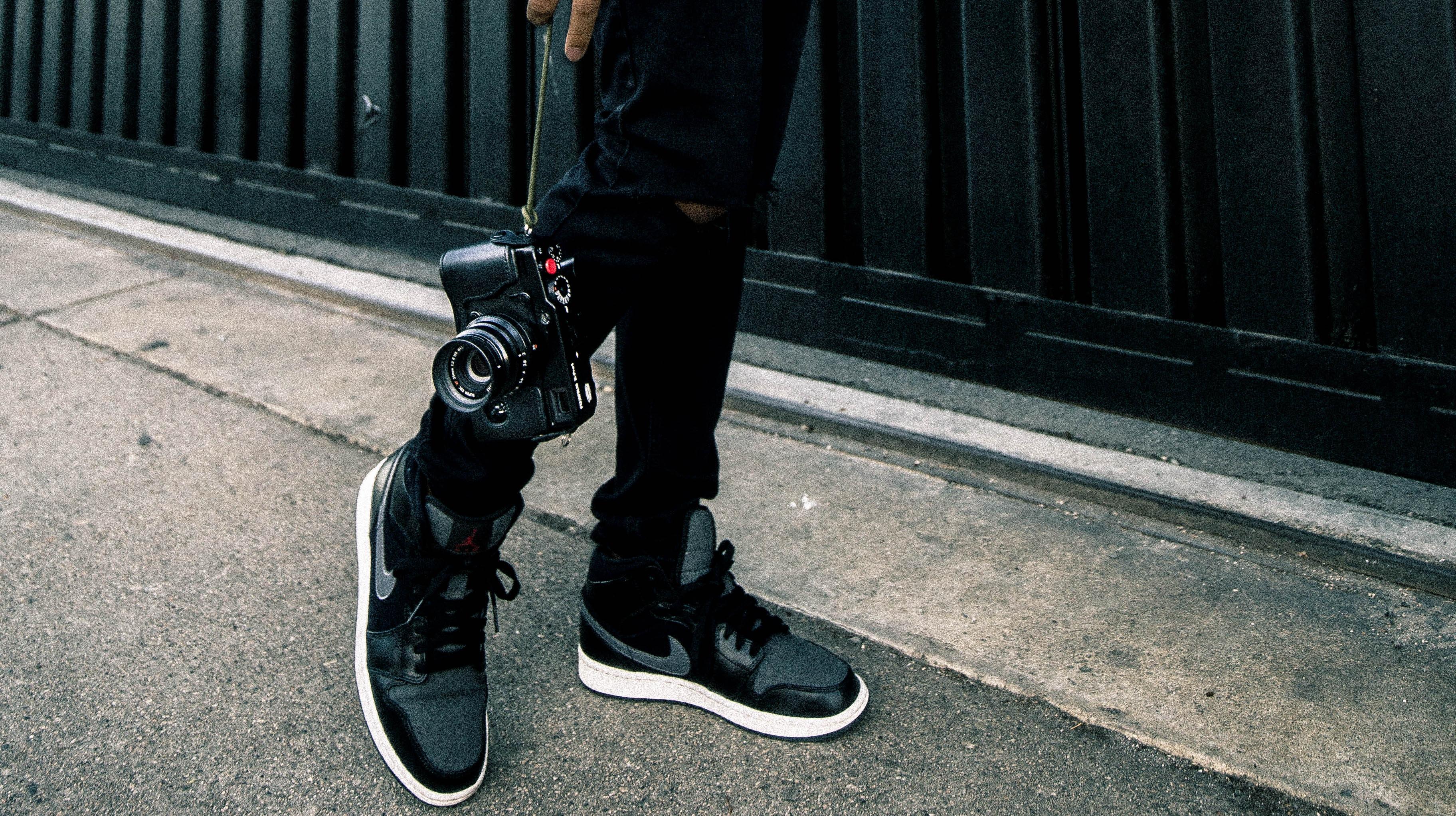 person holding black SLR camera