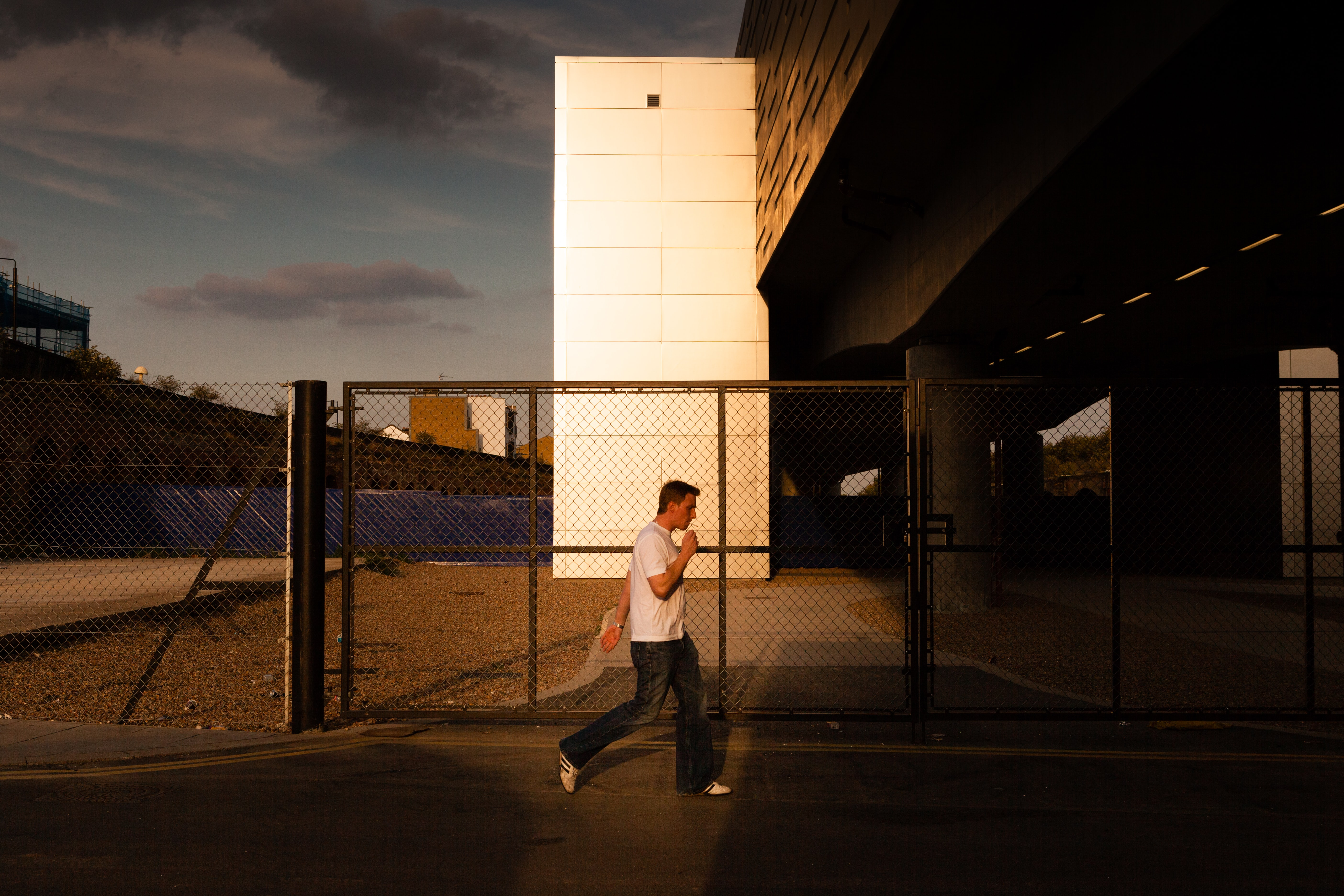 man walking in front of chain link fence