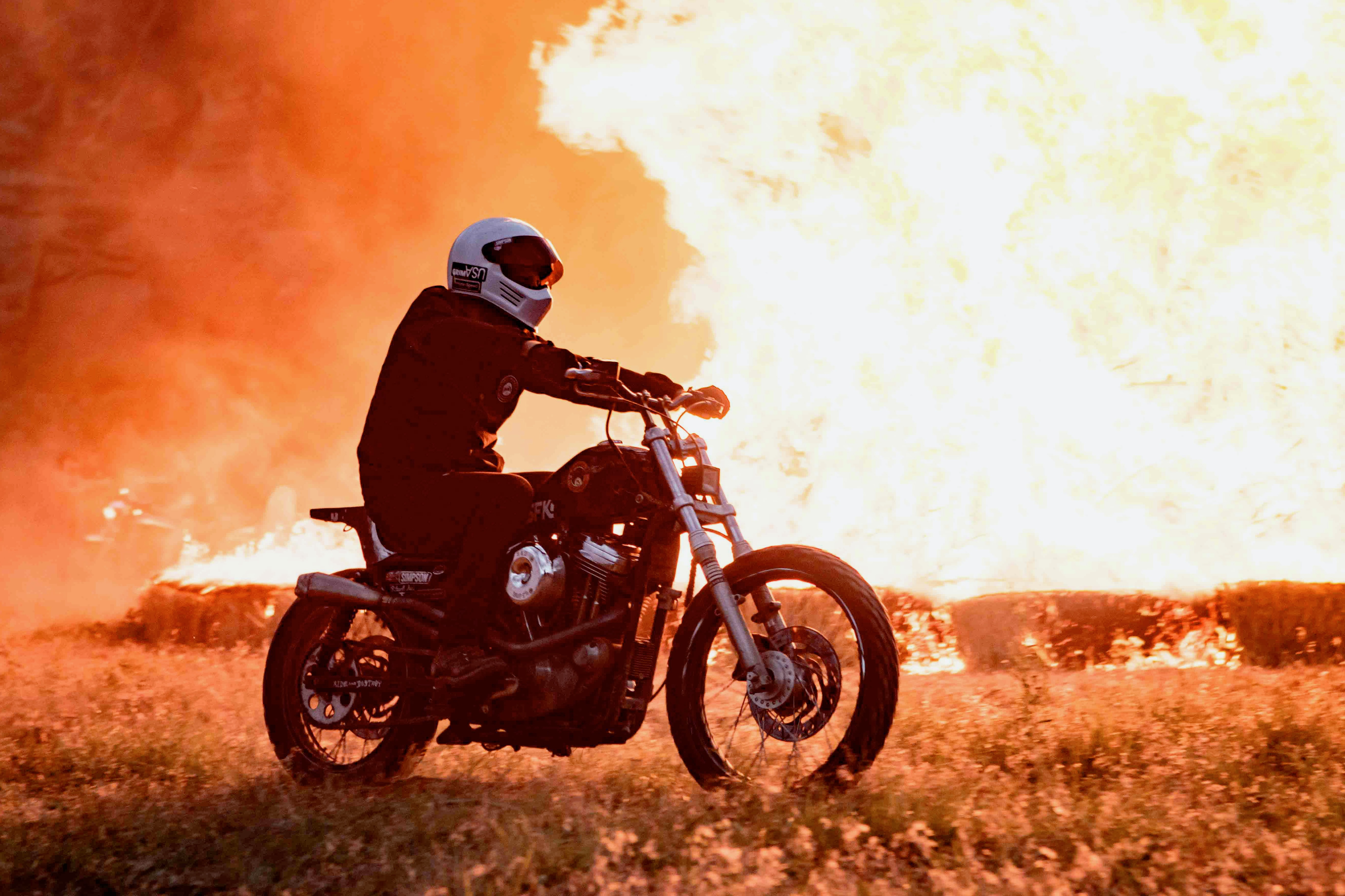 person riding motorcycle near burning structure