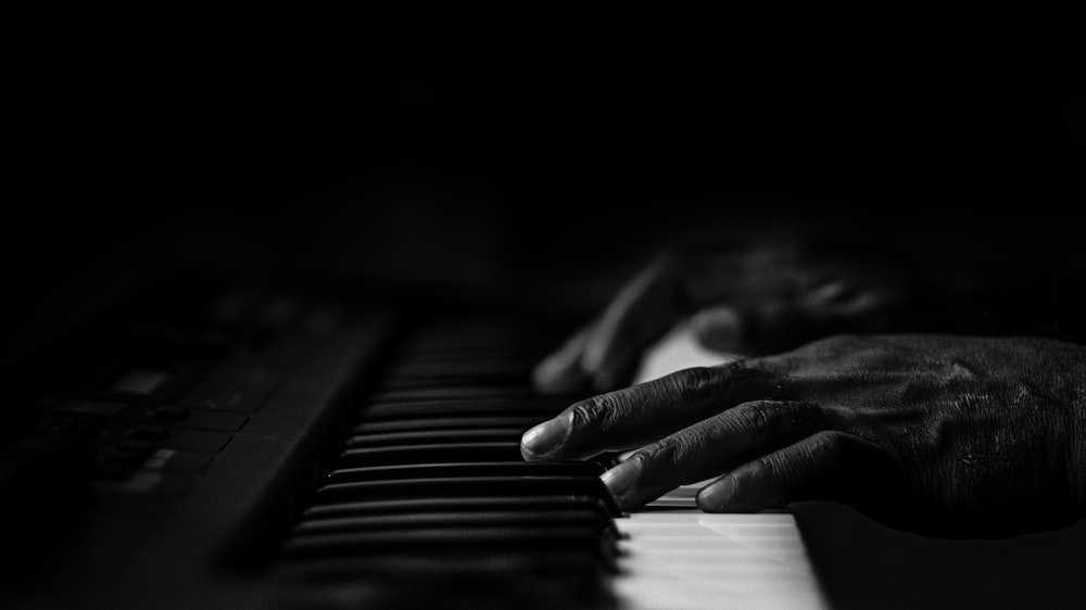 grayscale photo of person playing piano