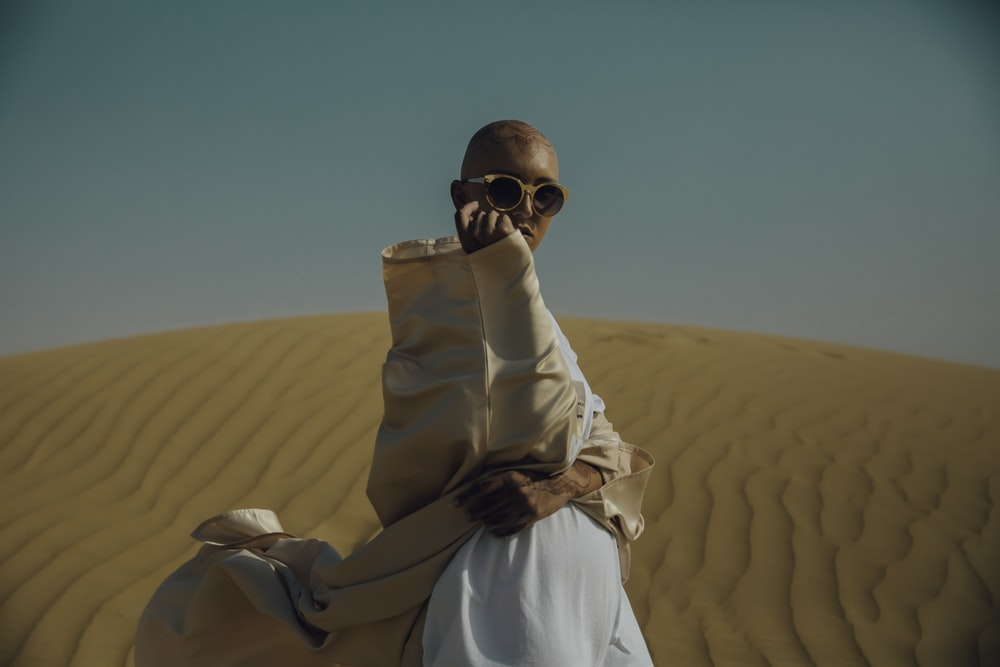 man in brown and white apparel on desert during daytime