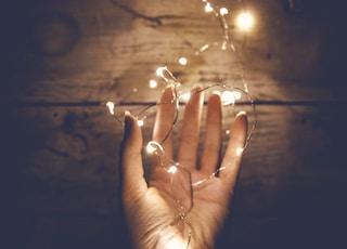 person holding white string light
