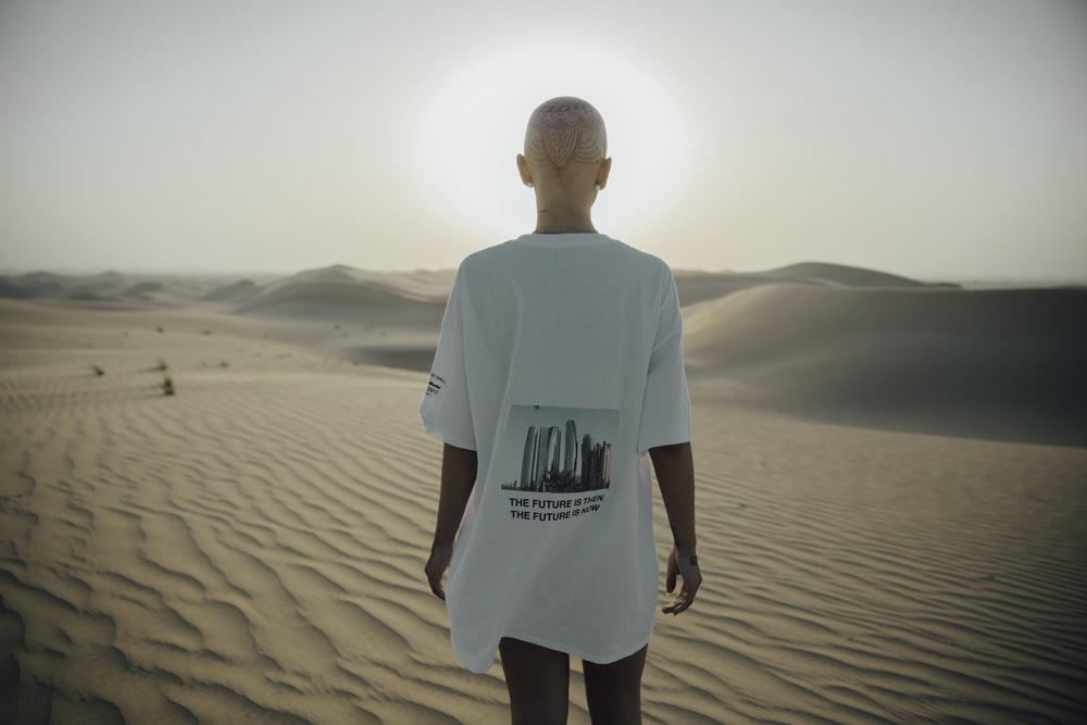 photography of woman standing on desert