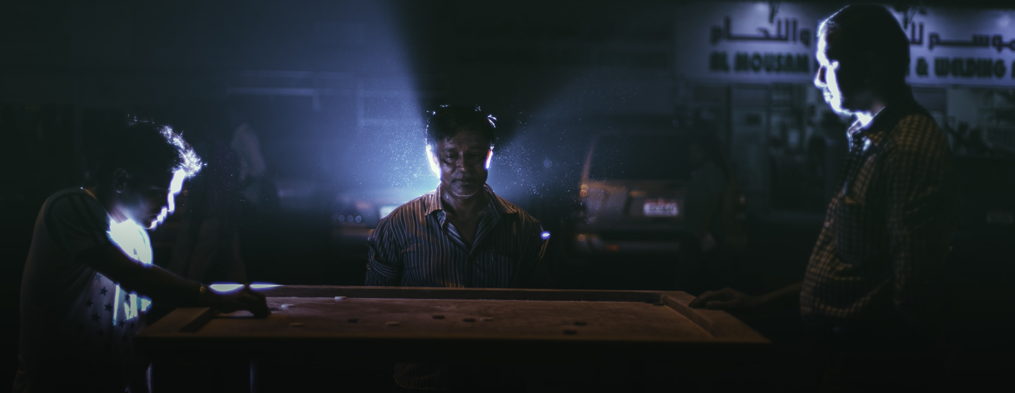 man standing on side of table film still