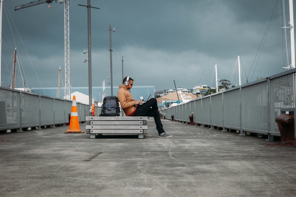 person sitting on bench wearing headphones
