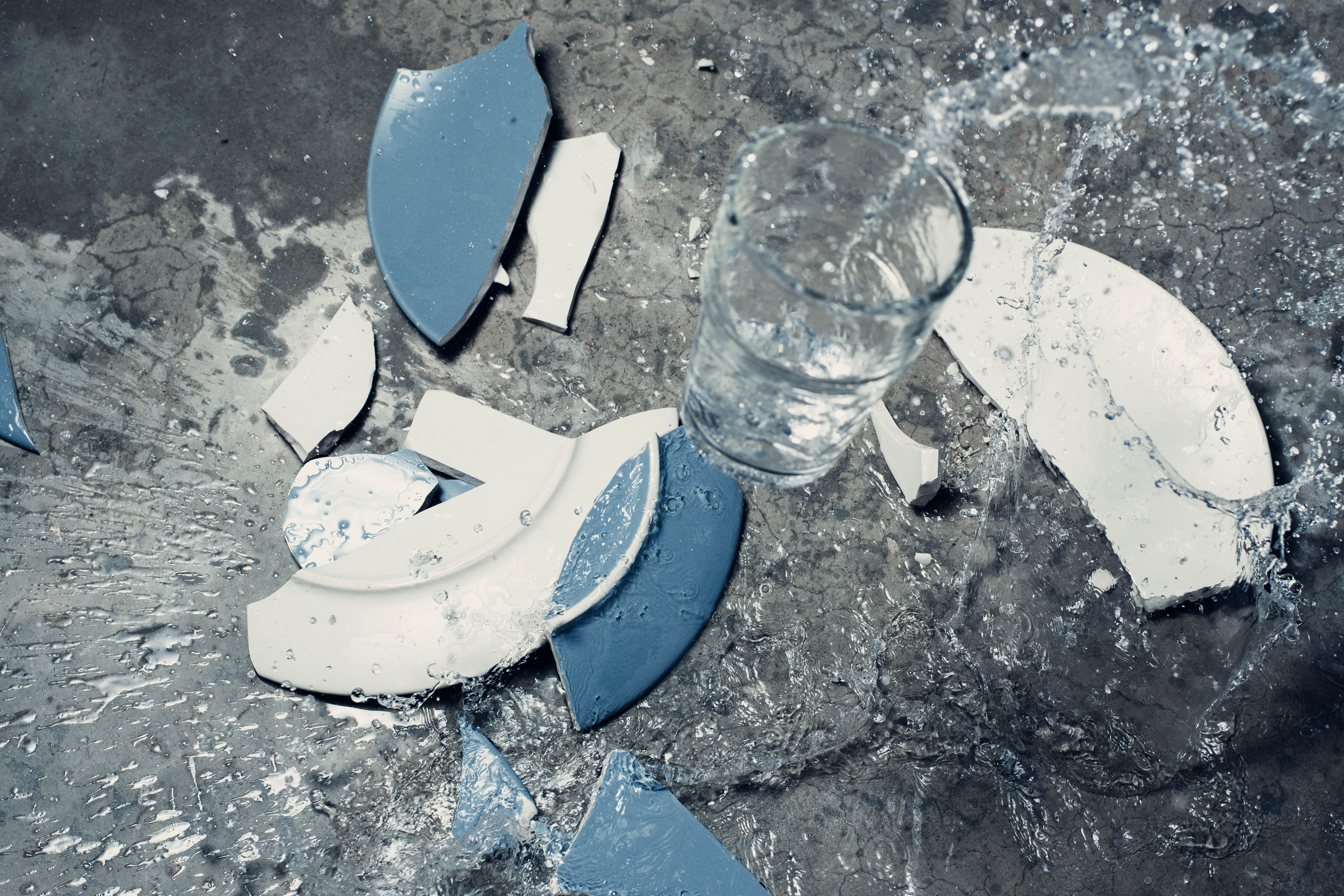 broken white and blue ceramic plate and clear beverage glass with water