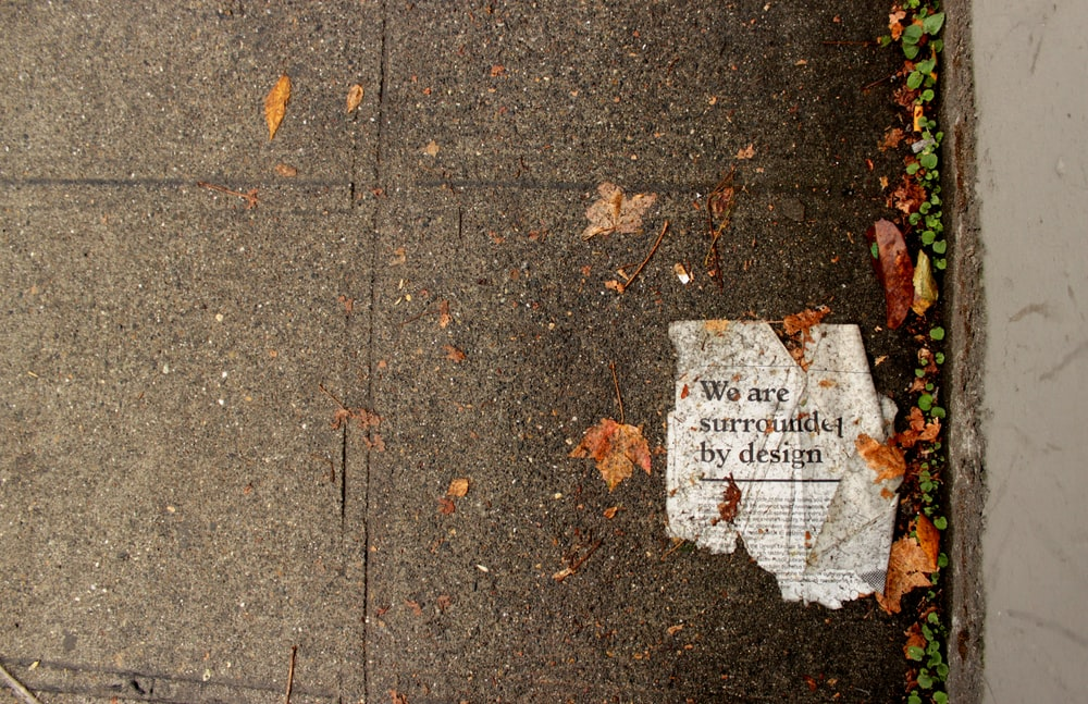 we are surrounded by design-printed newspaper on ground near dried leaves