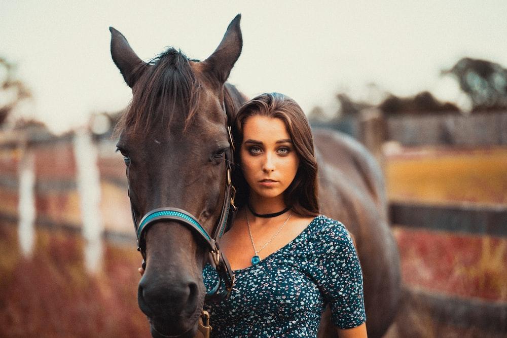 woman standing near brown horse