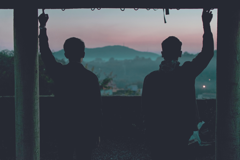 two mans facing mountain
