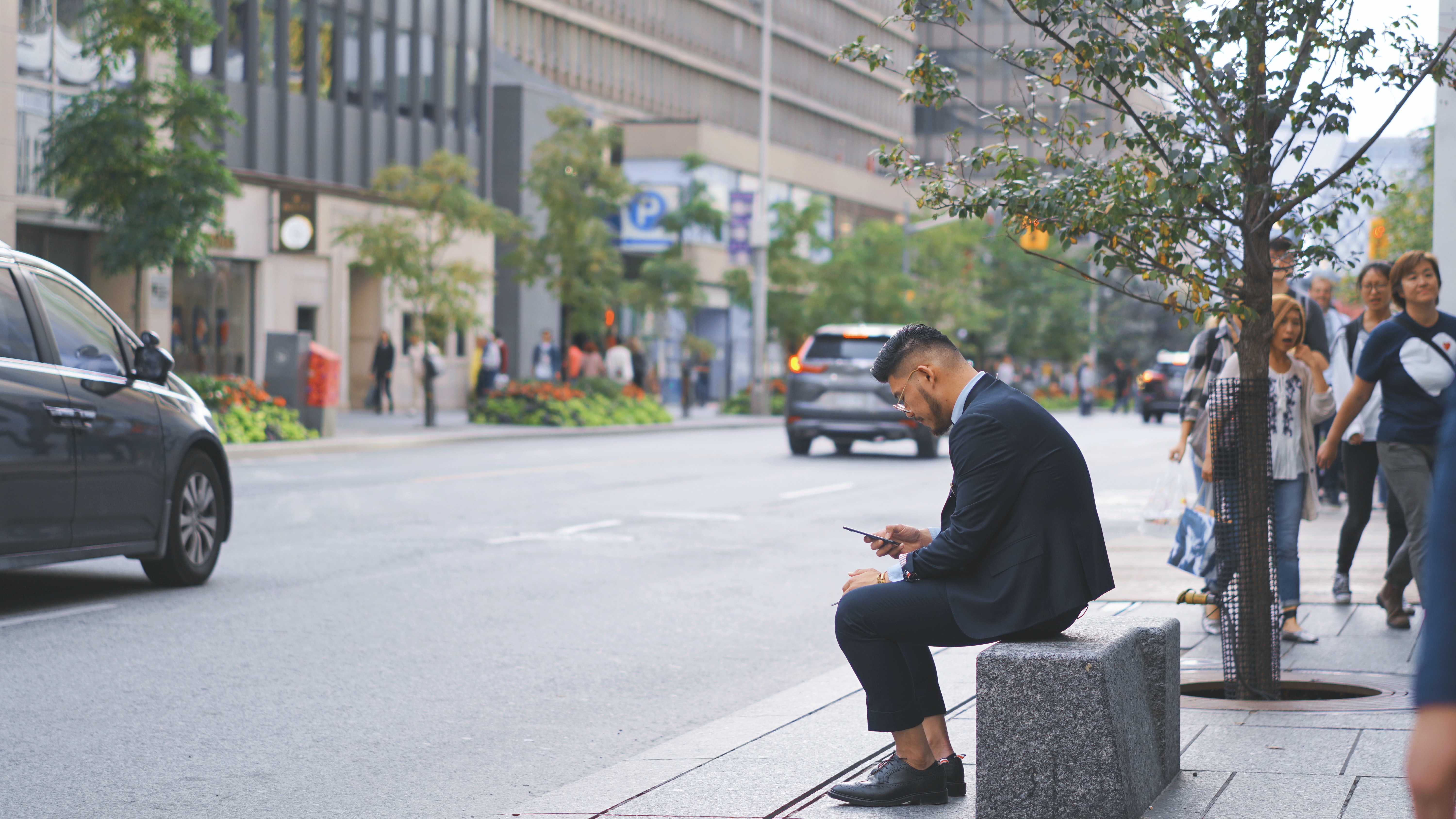 man with suit jacket sitting next to street with passing cars