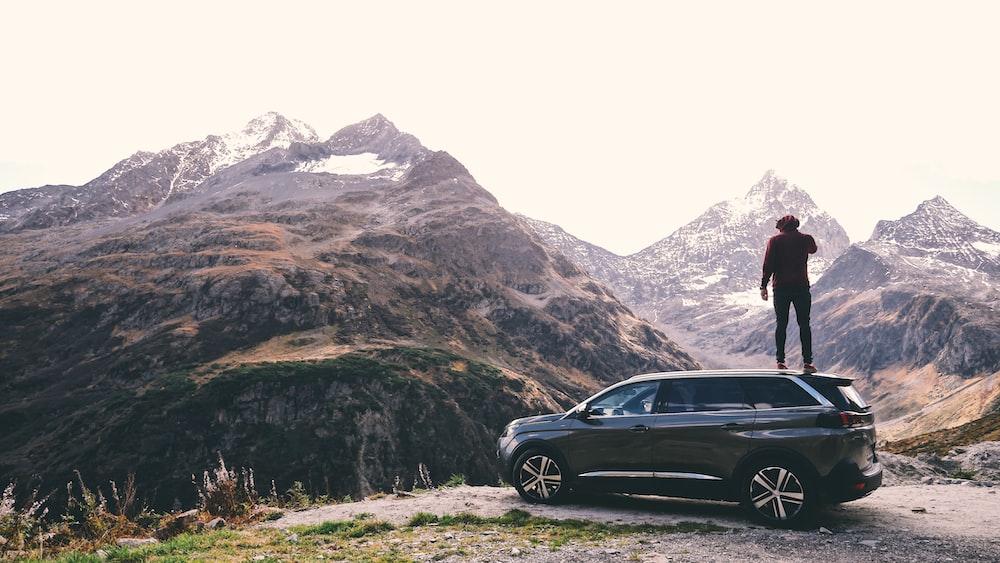 man standing on black 5-door hatchback across brown glacier mountains