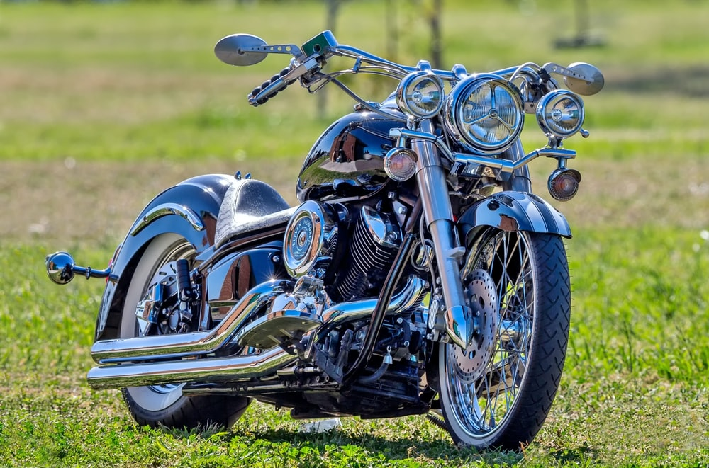 gray and black cruiser motorcycle parked at the grass fields