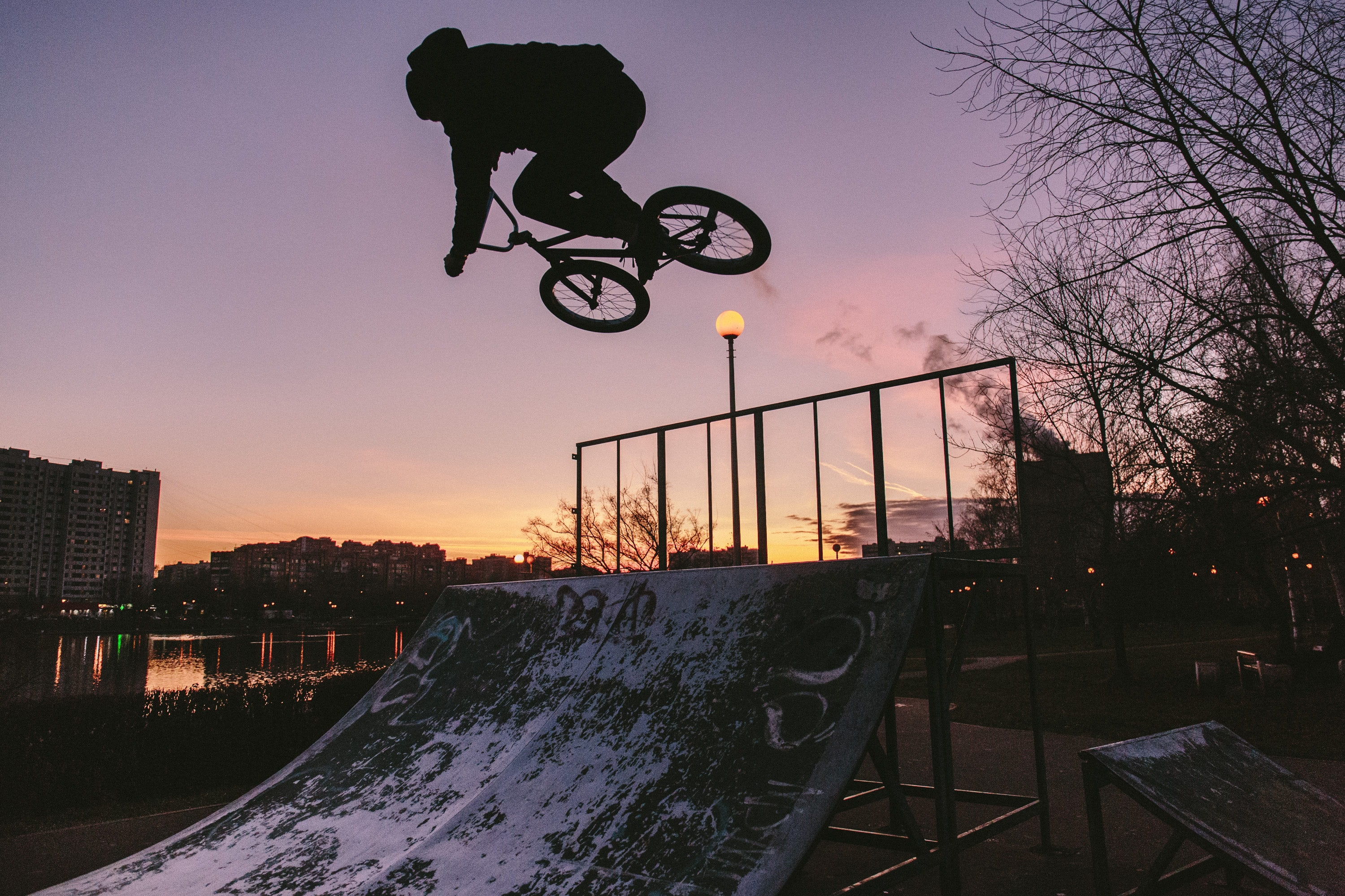 silhouette of person riding bike while doing tricks