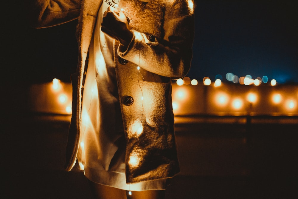 person in gray coat holding string light
