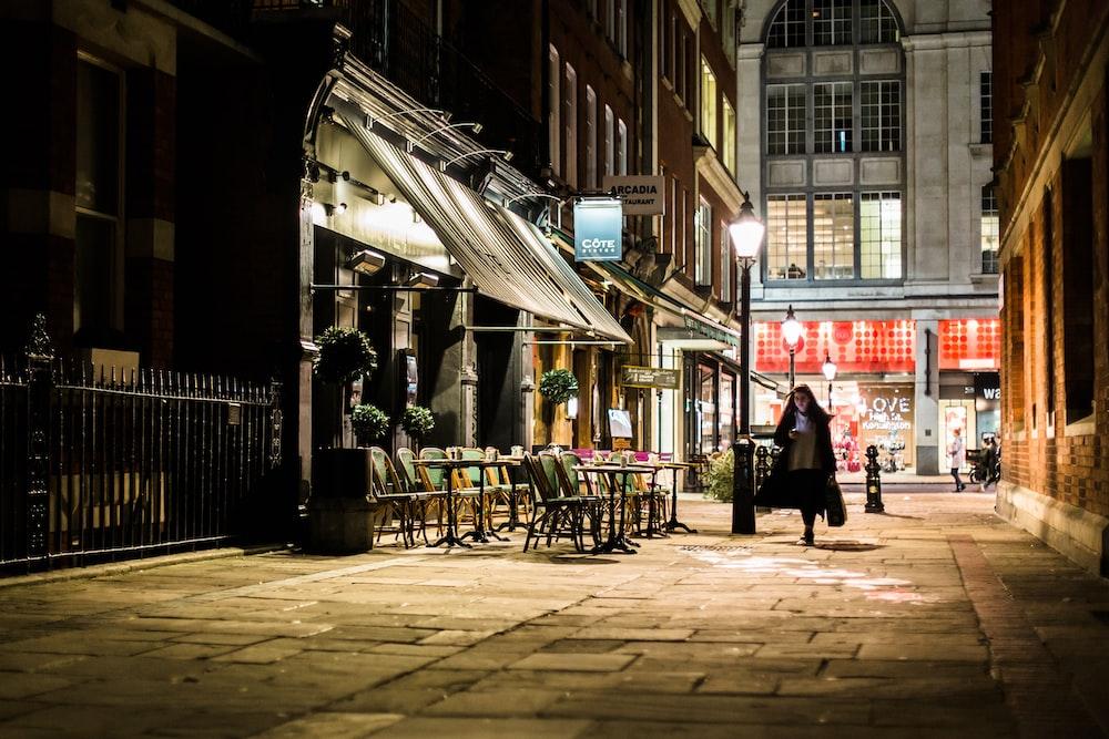 woman walking in alley near white store