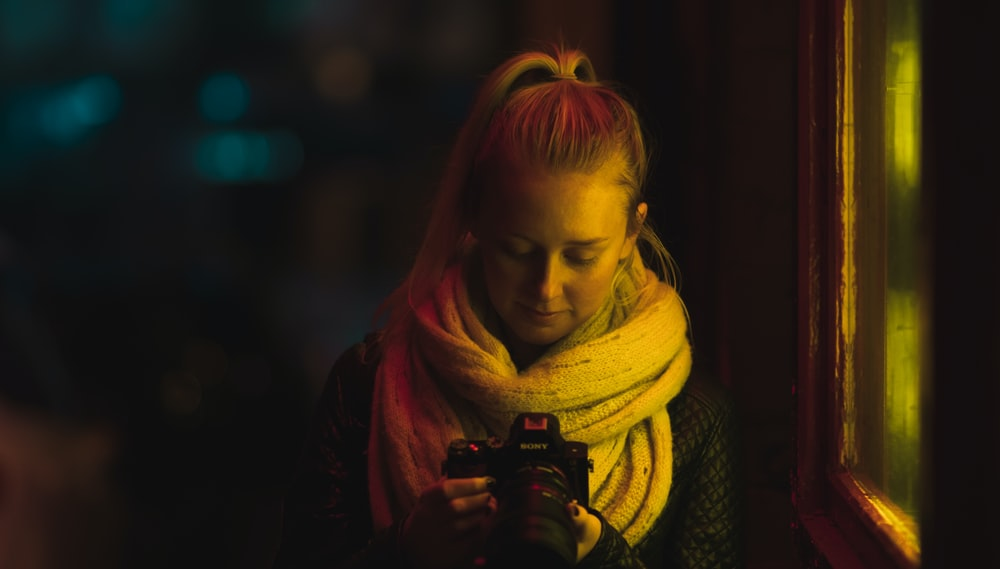 low light photography of woman in scarf using camera