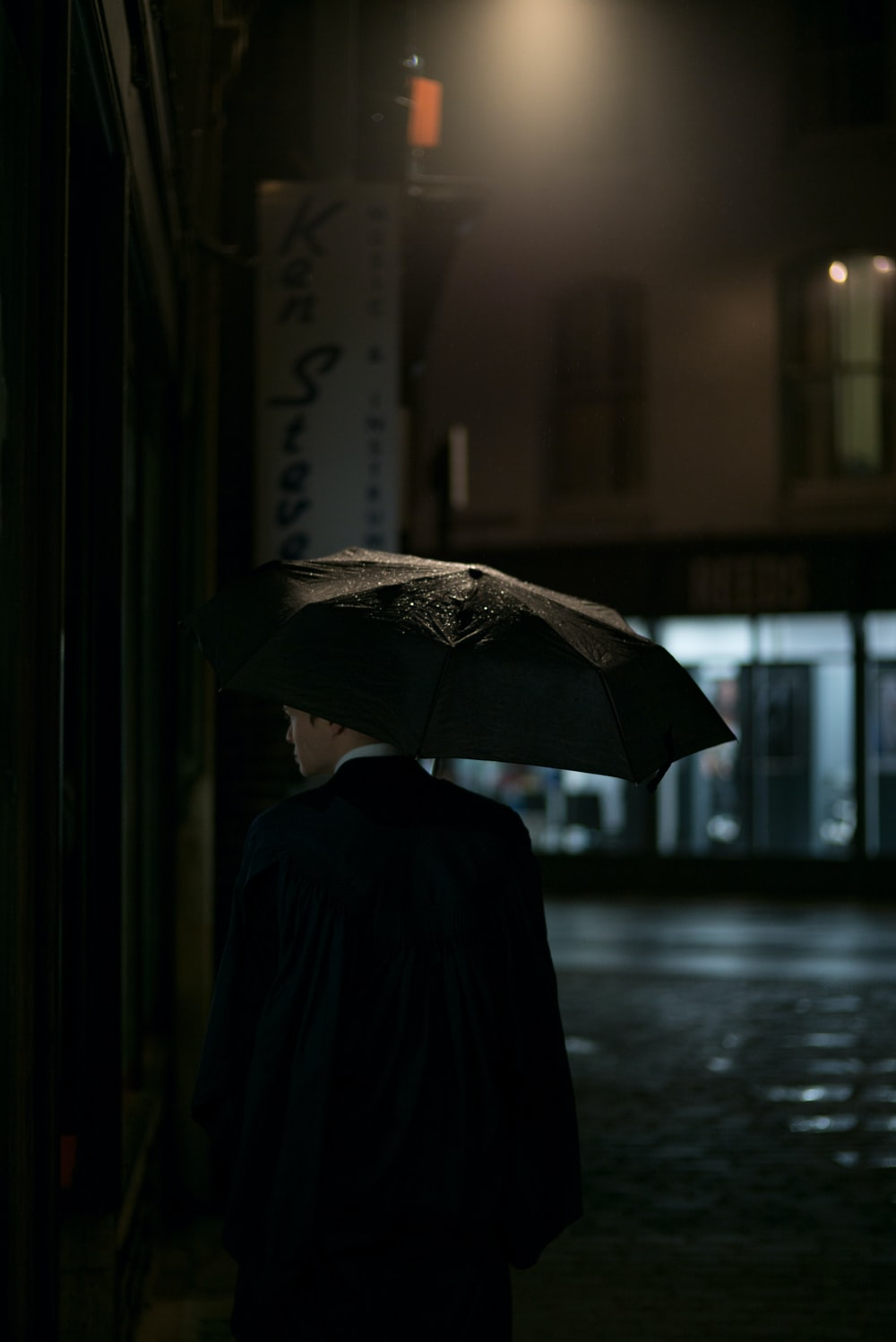 man in black suit jacket under umbrella