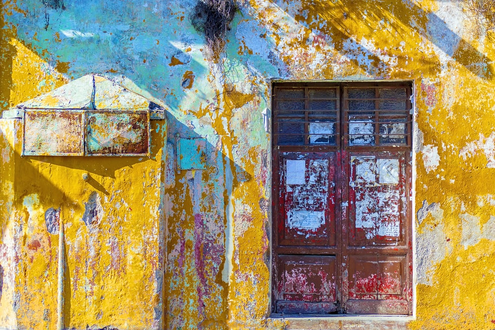 yellow, white, and teal painted concrete wall with red wooden 2-door window