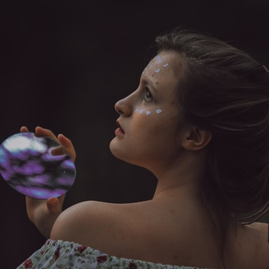 woman holding round purple and black stone