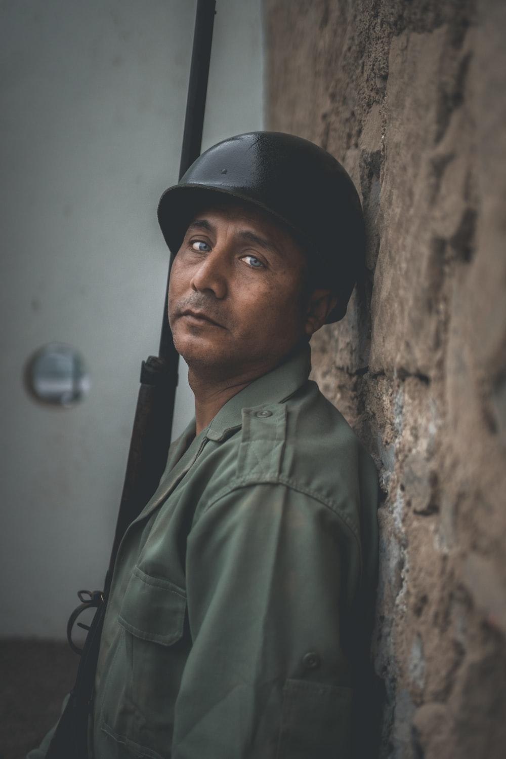 man wearing black hard hat while holding rifle