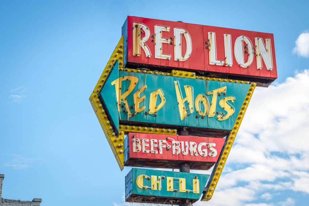 Red Lion, Red Hots, Beef Burgs, and Chili signage under white and blue cloudy skies
