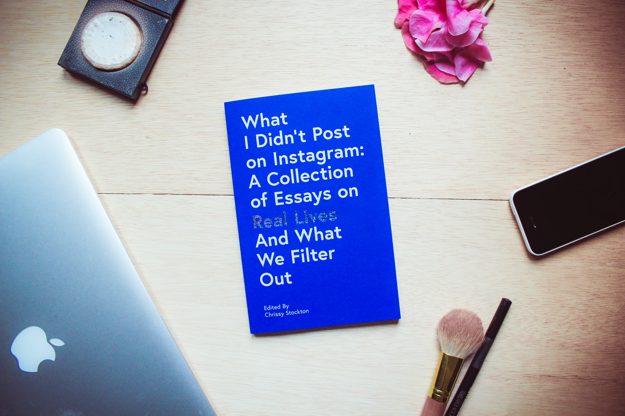 "A table or desktop setting of the book, ""What I Didn't Post on Instagram"" surrounded by objects one might use to prepare for a selfie (makeup, iPhone, laptop). We asked women to share the truth behind their Instagram photos for a collection of essays. The book 'What I Didn't Post On Instagram' by Chrissy Stockton exposes that we are all a little confused when it comes to life. We are all just trying to belong. The essays housed in this collection are deeply honest, real, and make you feel seen and connected as they reveal the humanness within a platform that has quickly become less than human."
