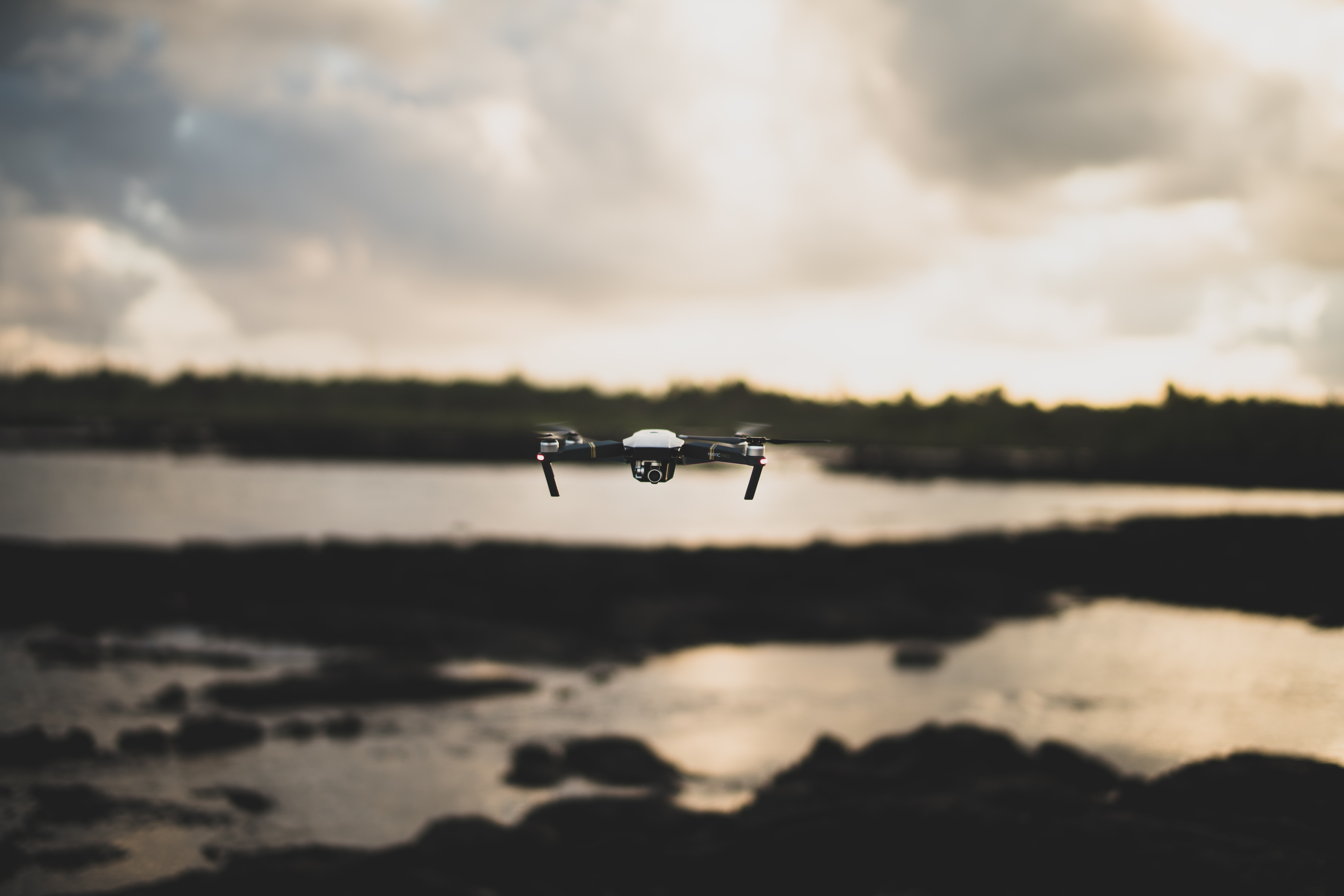 flying white and black drone during daytime
