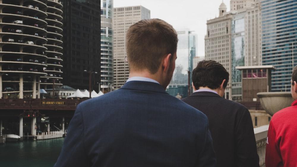 man wearing blue blazer standing behind two men during daaytime