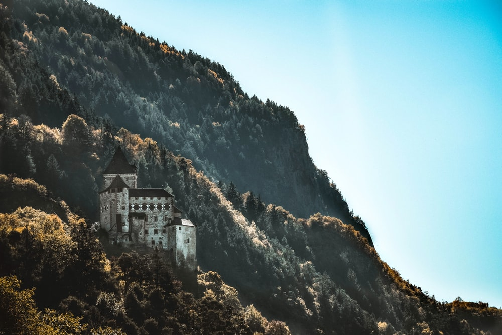 white concrete mansion on mountain under blue calm sky