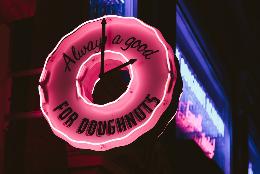 selective focus photography of lighted always a good for doughnuts clock signage