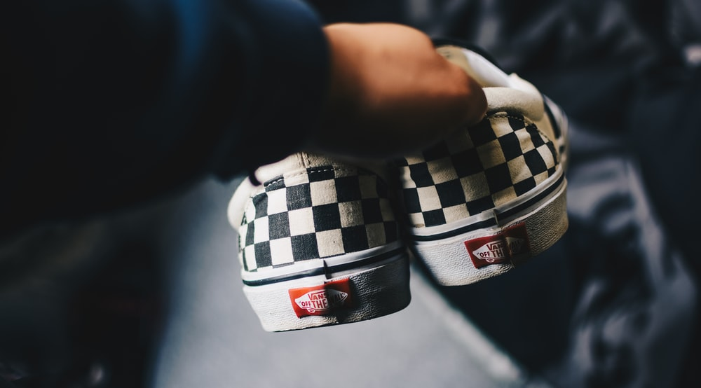 person holding pair of black-and-white checkered Vans Era low-tops close-up photograhy