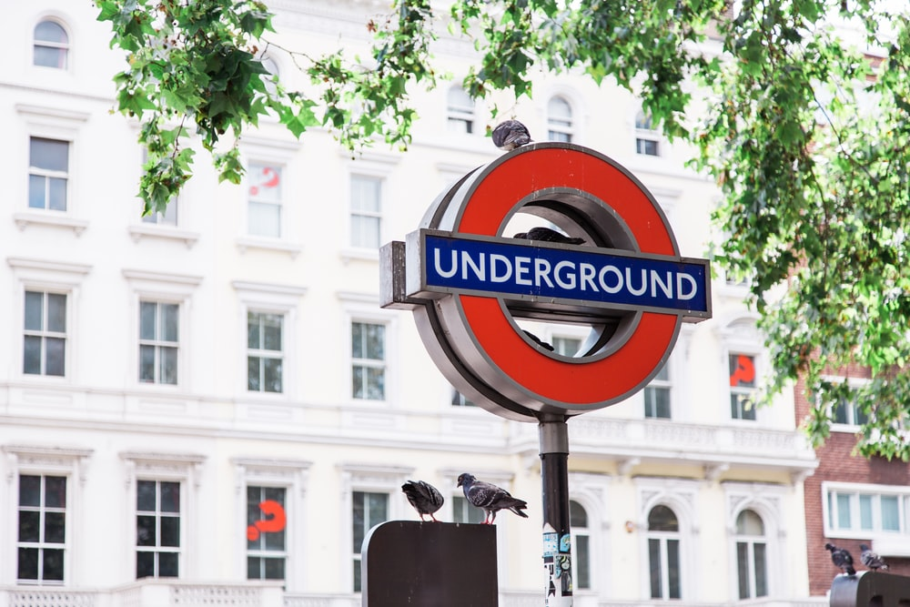 photo of red and black Underground street signage with two birds on top