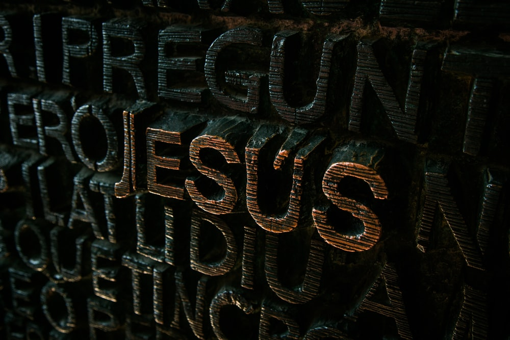 black and brown Jesus embossed sign