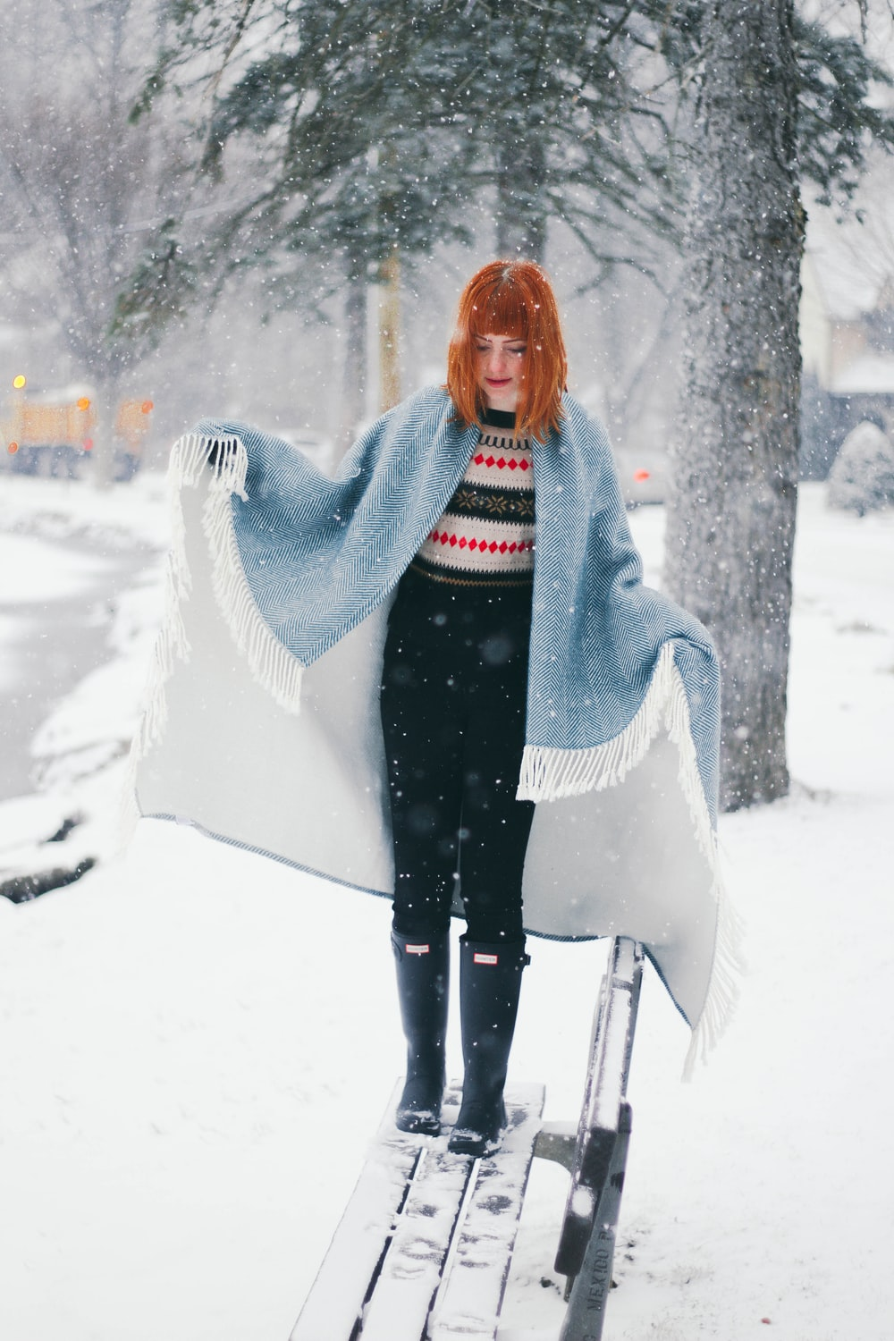 woman standing on snow covered bench while snowing during daytime