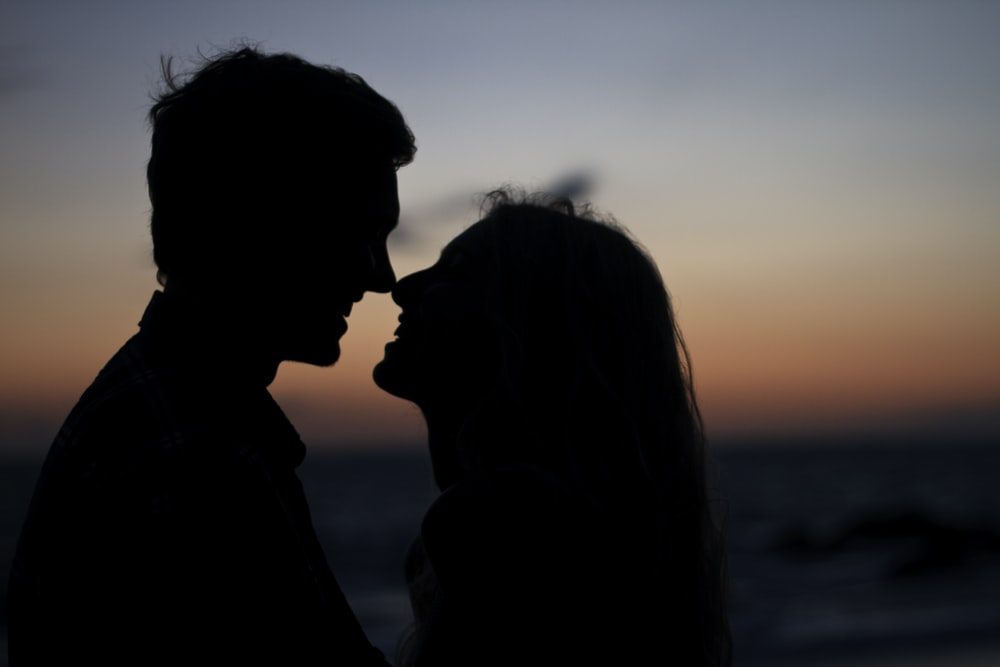 silhouette of man and woman about to kiss on beach during sunset