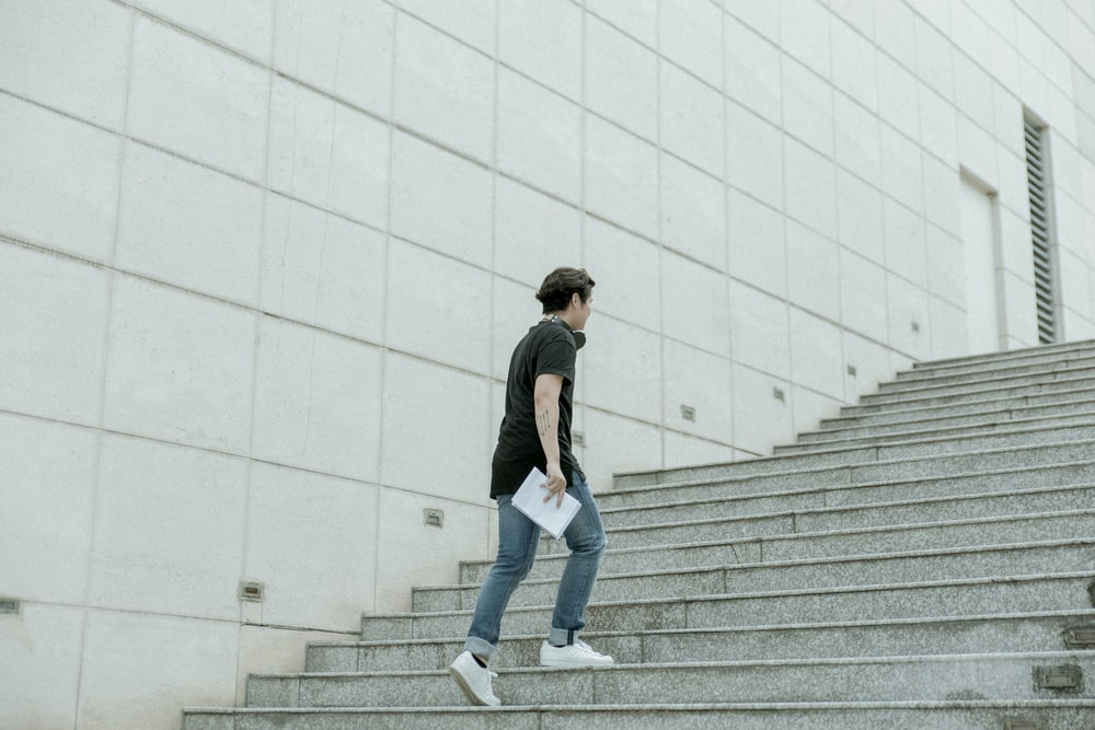 man holding white blanket paper walking on gray stair