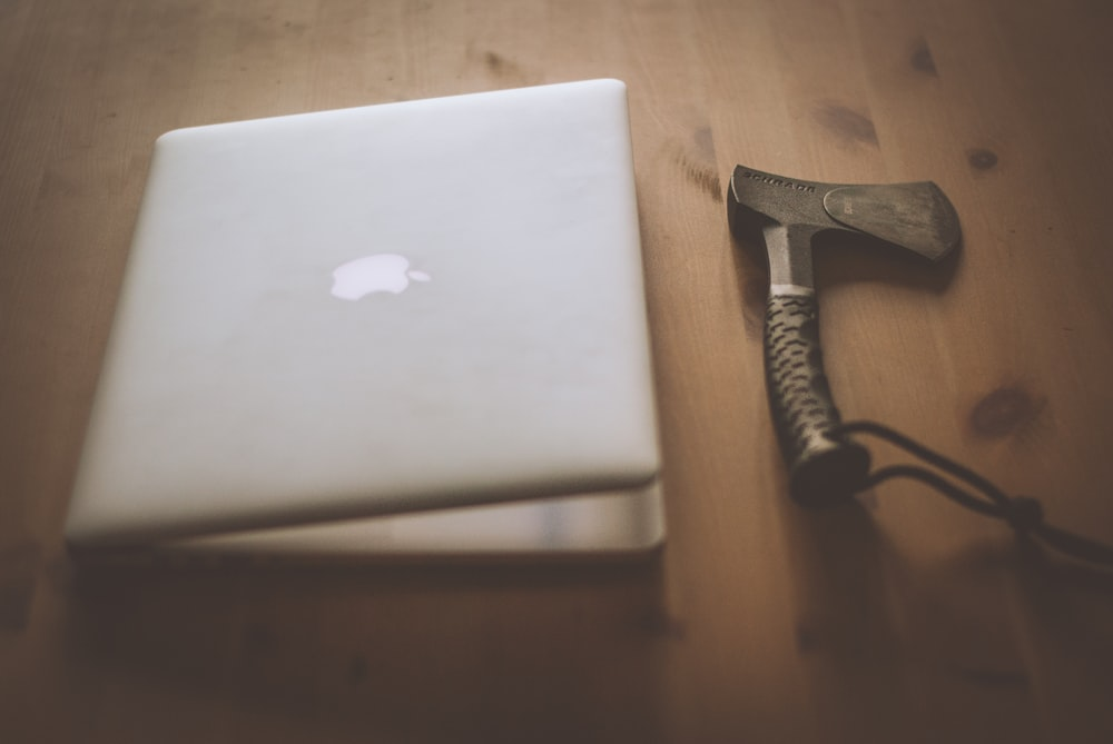 silver MacBook and black handheld tool