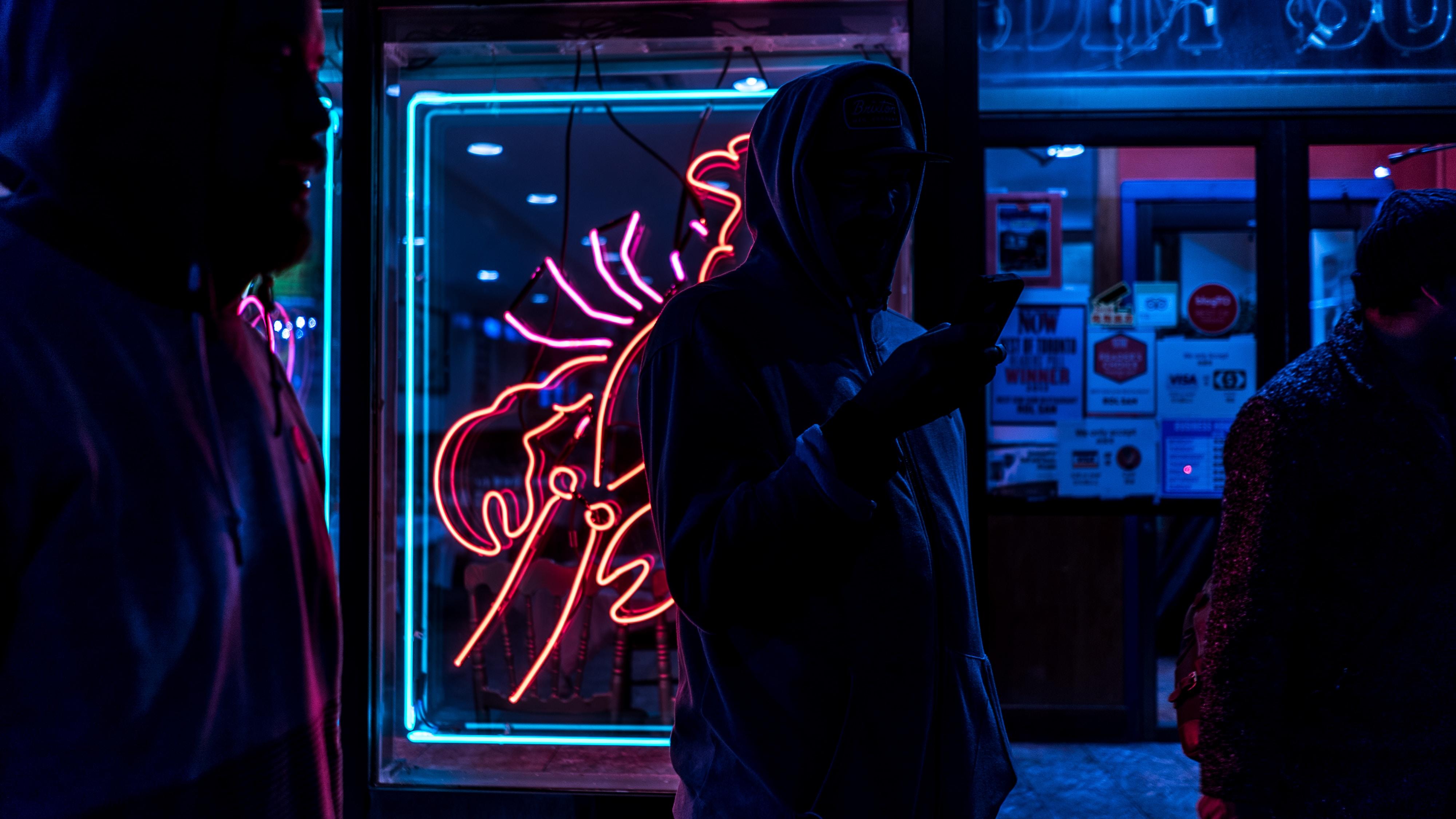 man standing holding smartphone