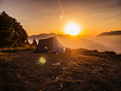 dome tent on mountain top with sun as background photo camping zoom background